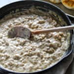 Sausage gravy in skillet with wooden spoon.