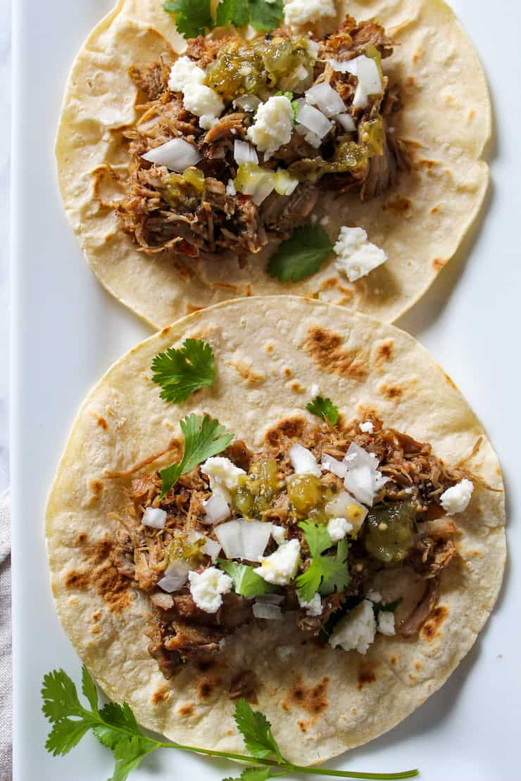 Tacos de carnitas with toppings on tortilla.