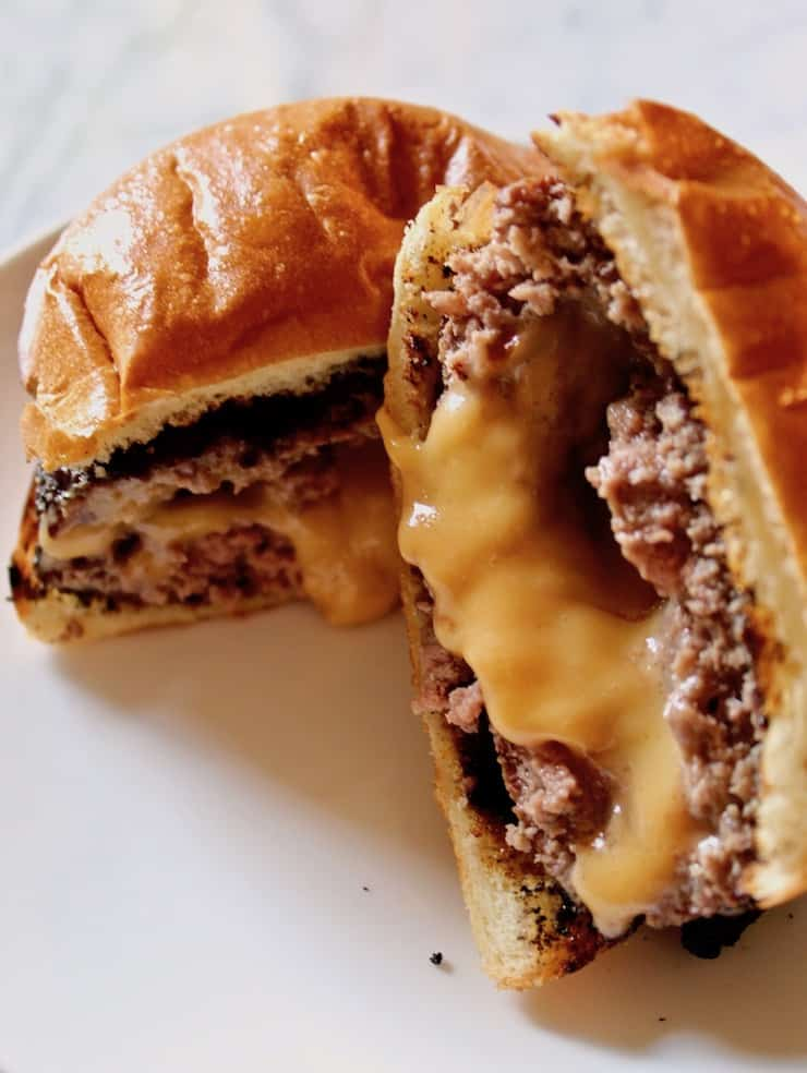 Juicy Lucy Burger, burger cut in half with cheese oozing out.