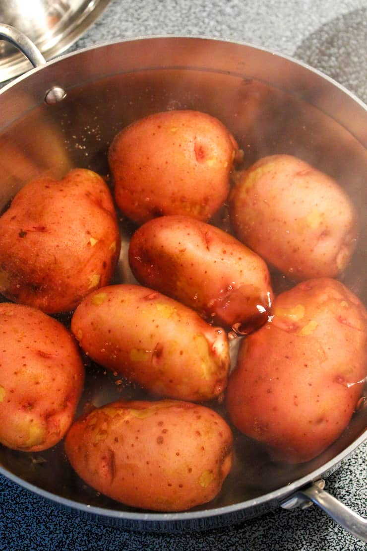 Red potatoes boiling in pot.