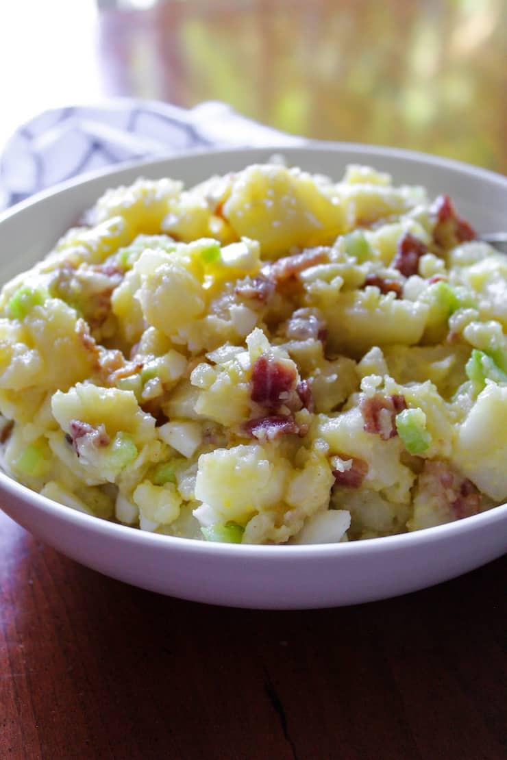 German potato salad in white serving bowl.