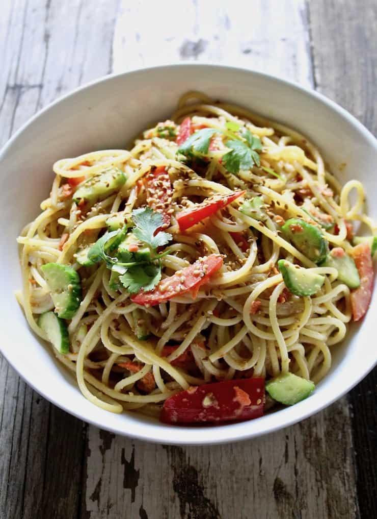 Peanut Sesame Noodles, in serving bowl on board.