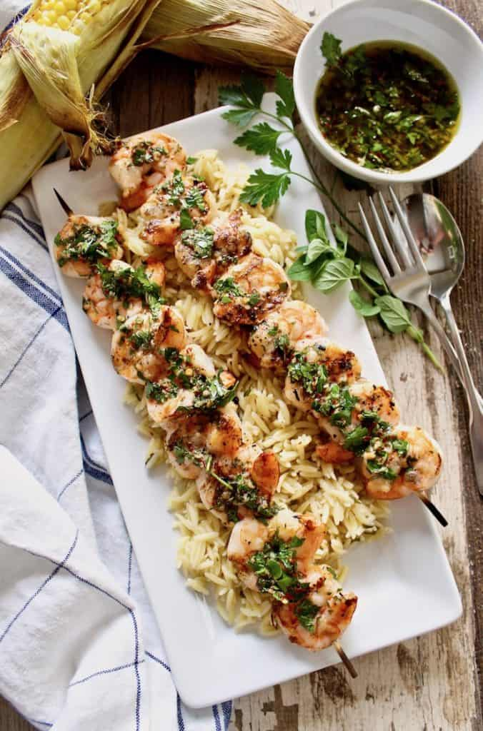 Grilled Shrimp with Chimichurri Sauce on platter with orzo.