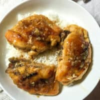 Chicken breast on white plate with rice.