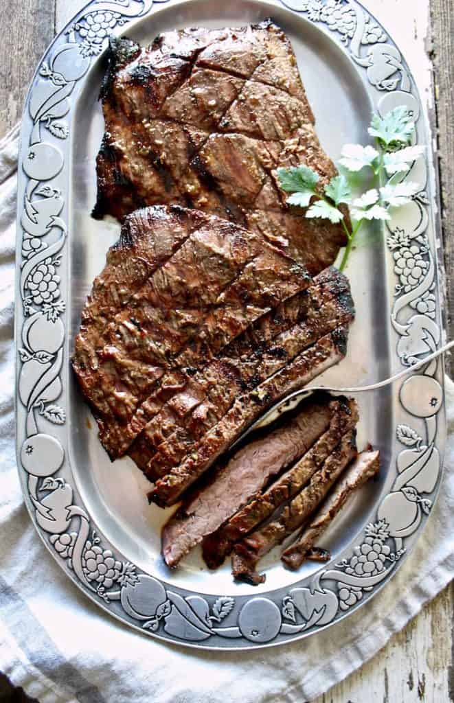 Grilled flank steak on platter, sliced.