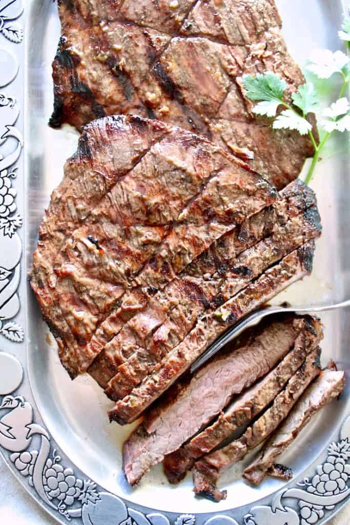 Marinated Grilled Flank Steak on serving platter.