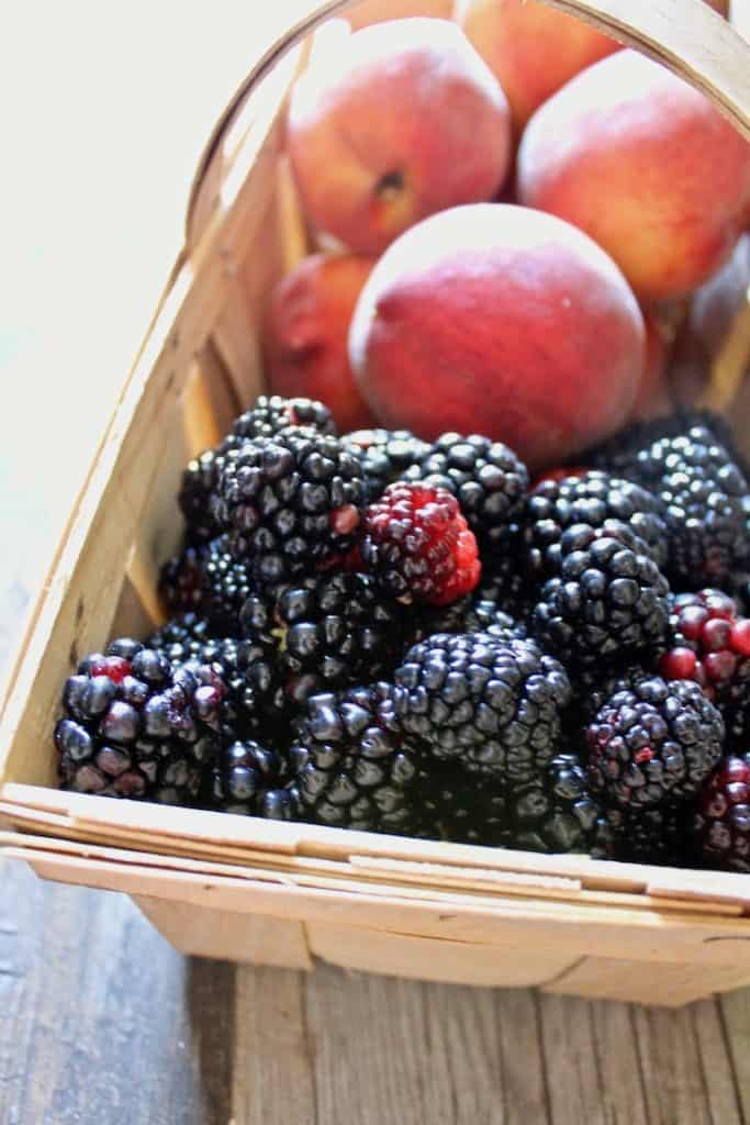 Basket of just picked blackberries and peaches from the farm.
