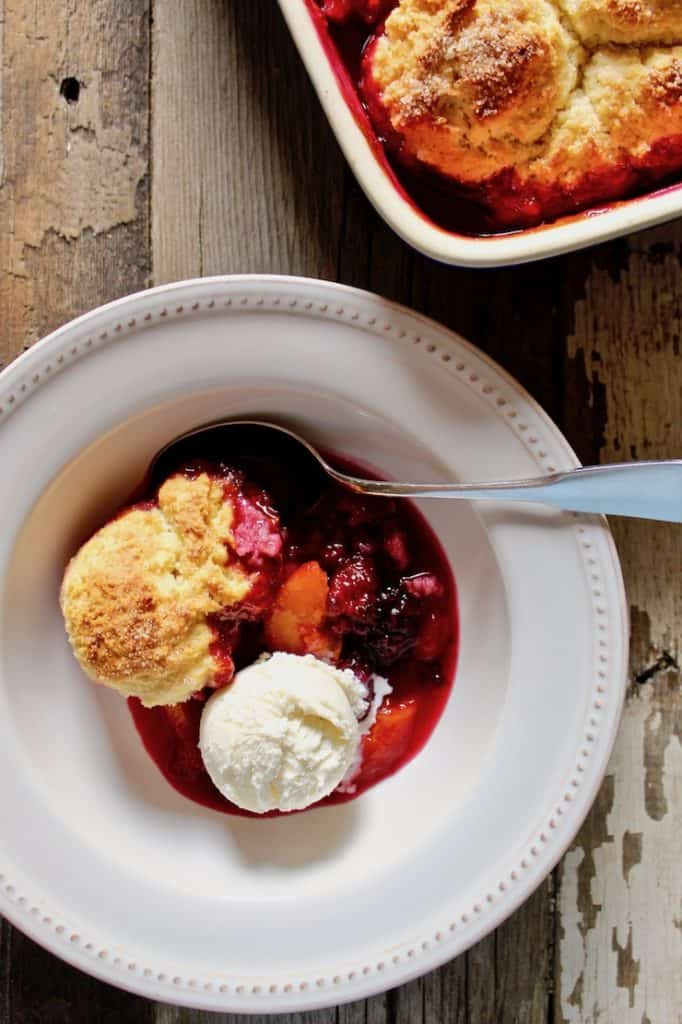 Cobbler in bowl with ice cream and spoon.