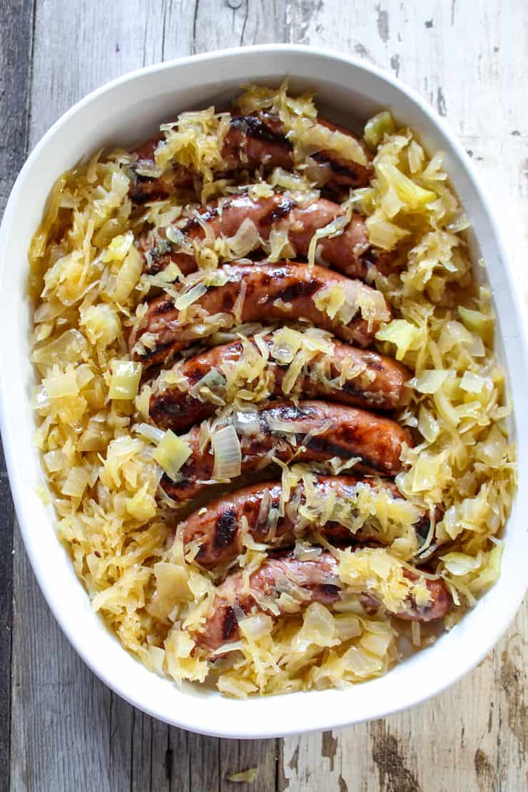 Bratwurst sausages grilled with beer and sauerkraut in serving dish.