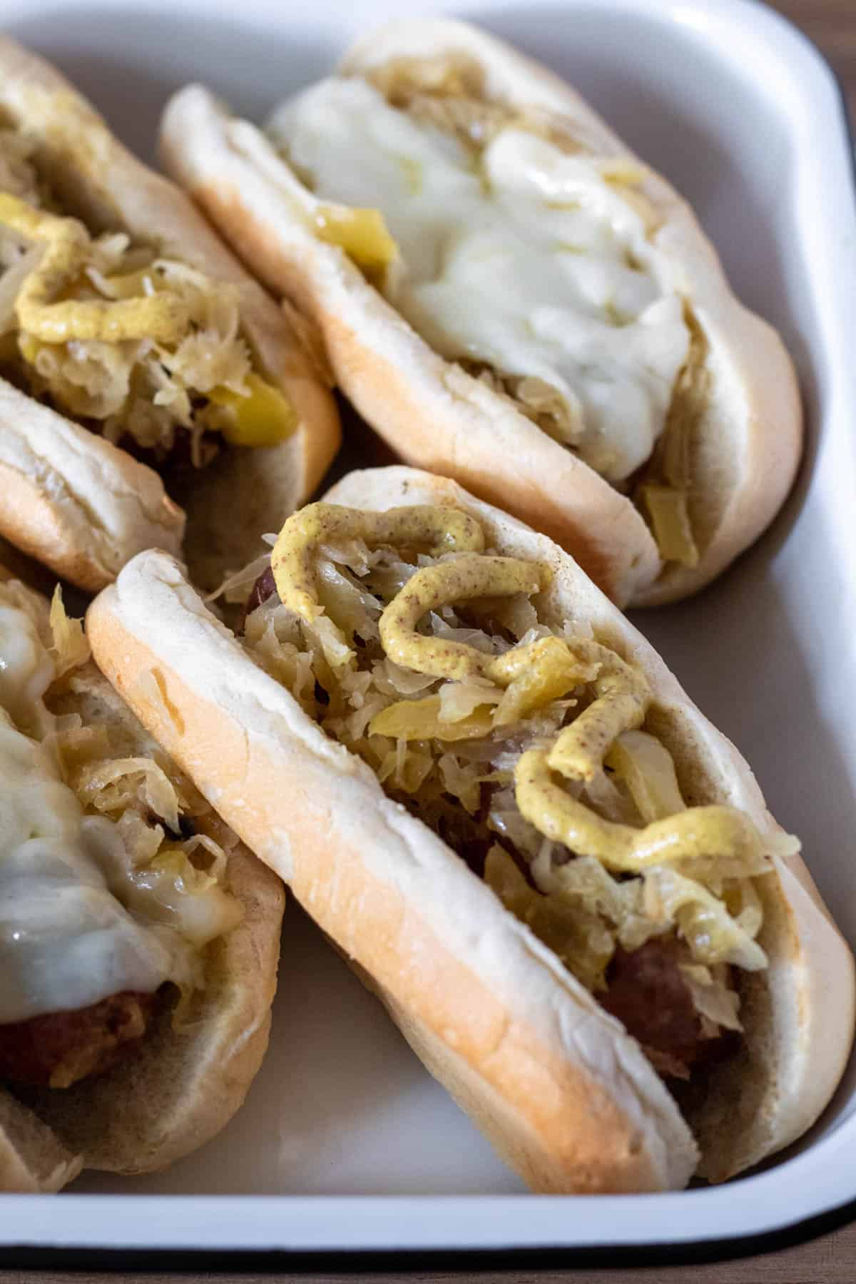 Closup of brats on buns with mustard and melted cheese.