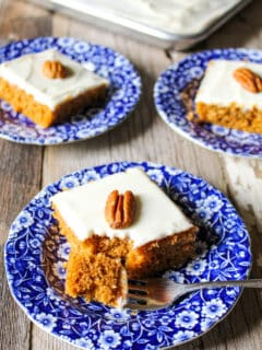 Pumpkin bars on several blue plates with pecan on top.