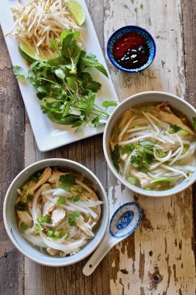Instant Pot Pho Ga, overhead of two bowls of pho and condiments