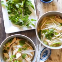 Bowls of pho ga surrounded with condiments