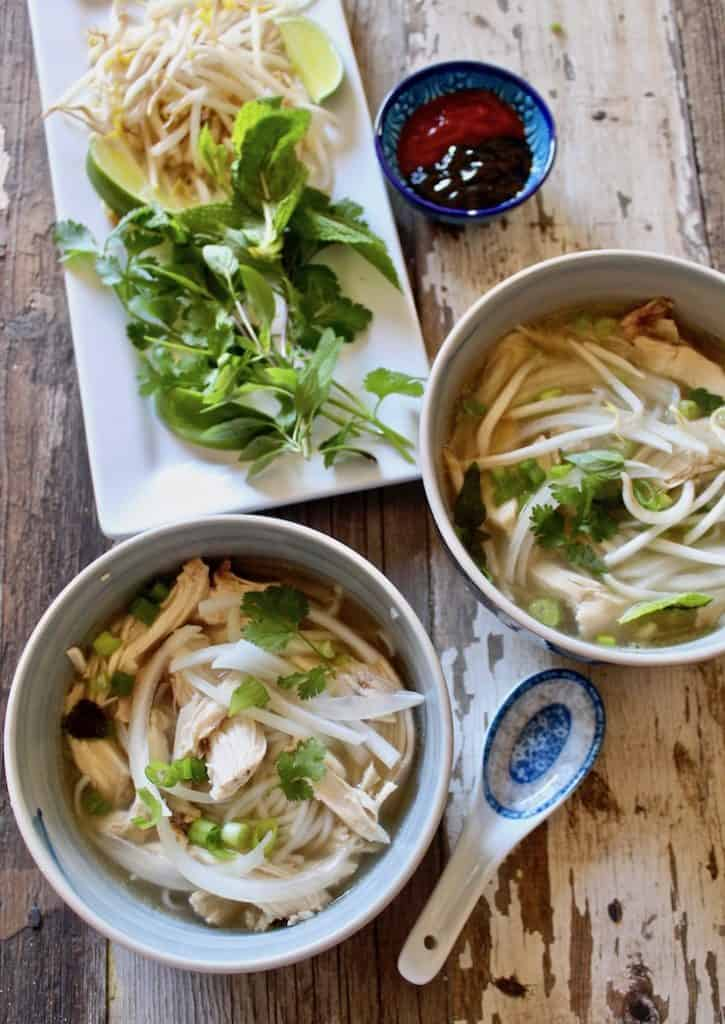 Instant Pot Pho Ga, two bowls of pho with condiments and spoon
