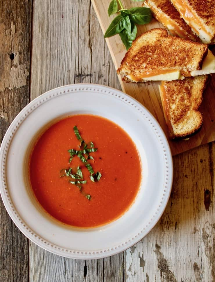 Soup in bowl with basil and side of grilled cheese.