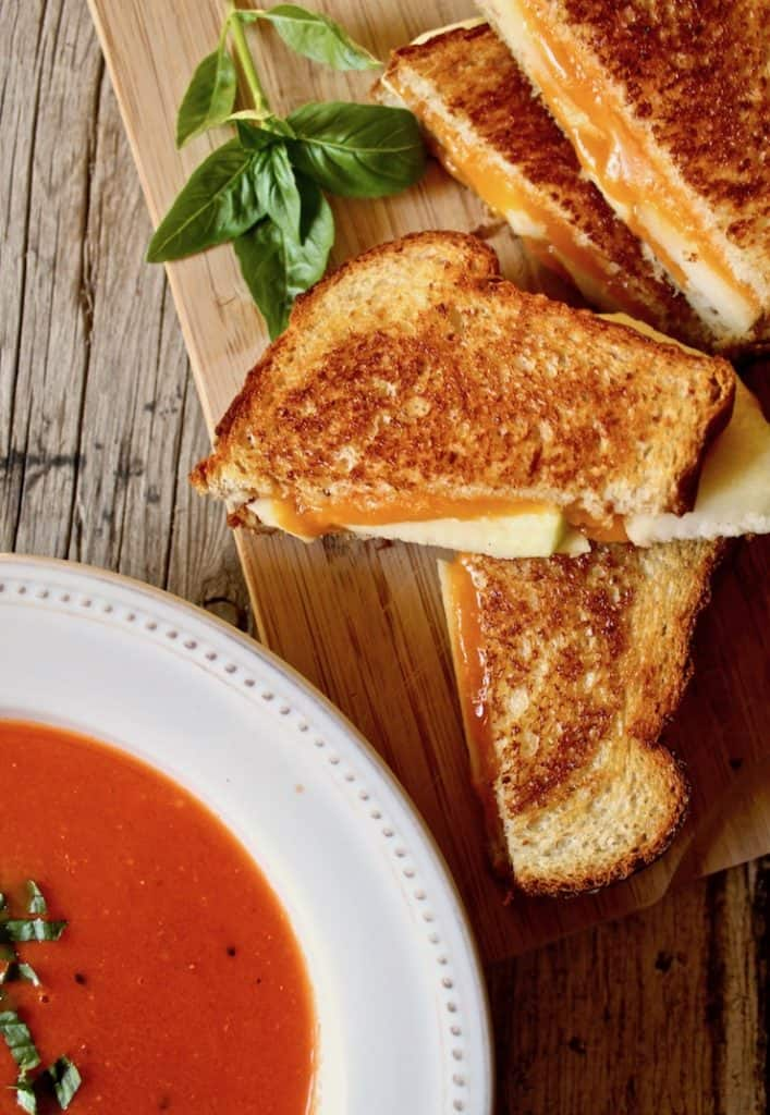 Grilled cheese and apple next to bowl of tomato soup.