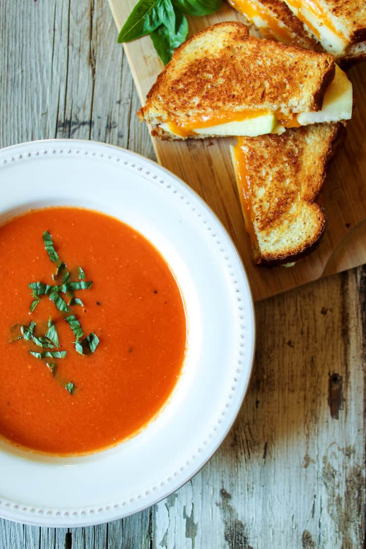 Bowl of soup and grilled cheese on the side.