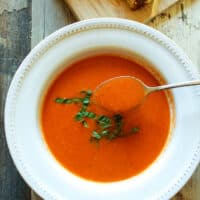 Spoonful of tomato bisque hovering over bowl of soup.