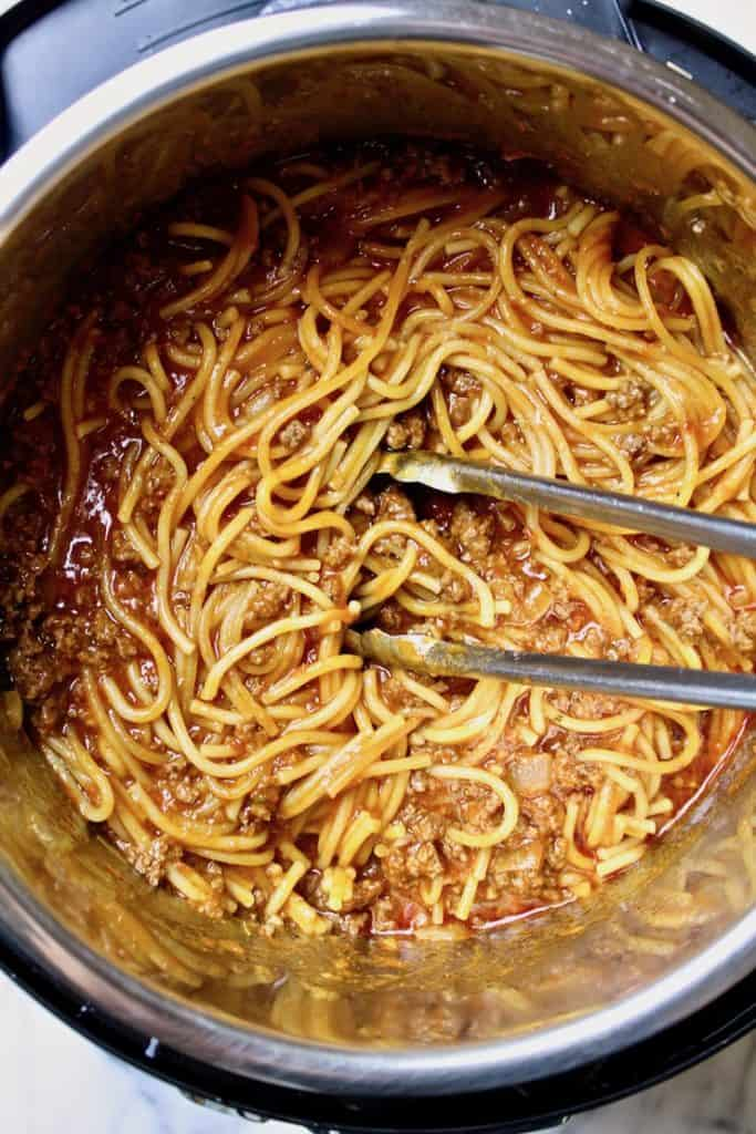 Instant Pot Spaghetti with Meat Sauce, in pressure cooker cooked and mixed with tongs