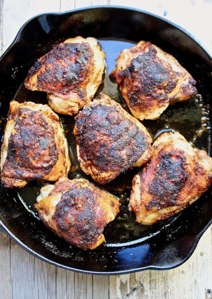 Overhead of blackened chicken thighs in skillet.