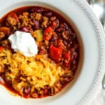 Turkey chili in bowl with sour cream and cheese.