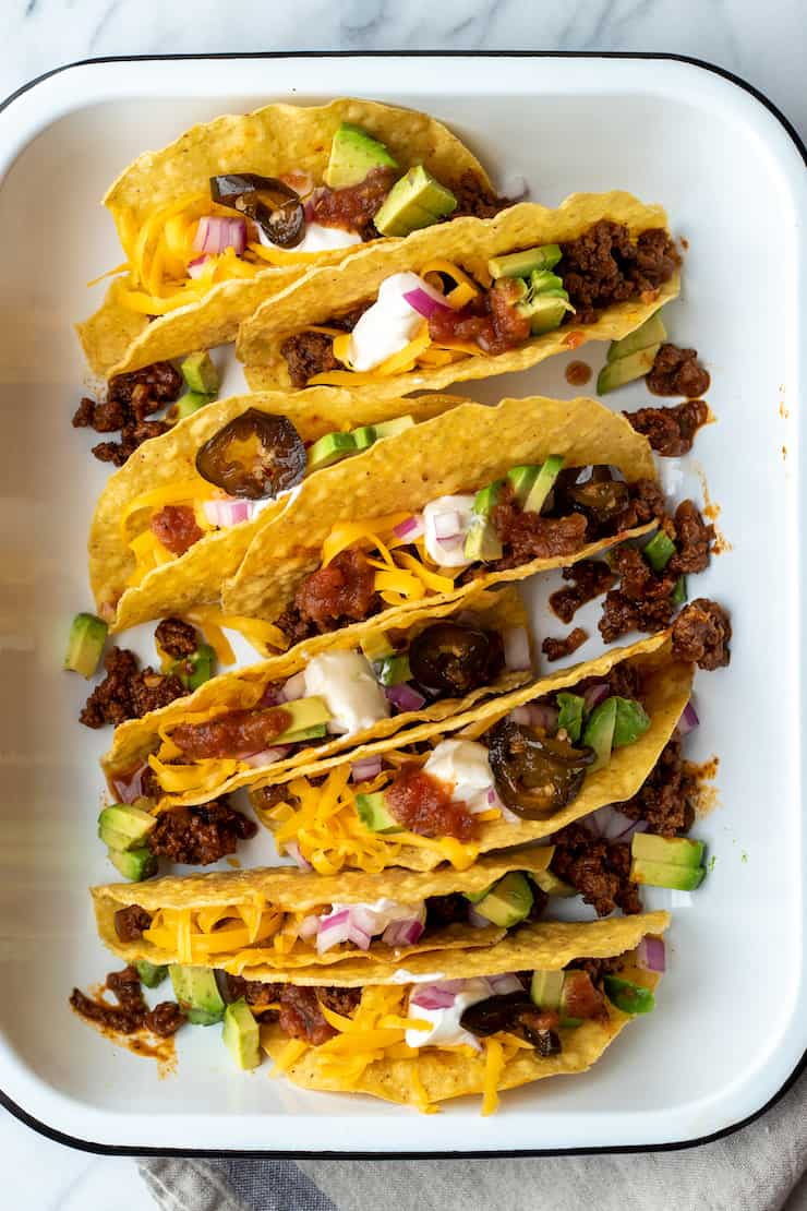 Beef tacos in hard shells in pan with toppings.