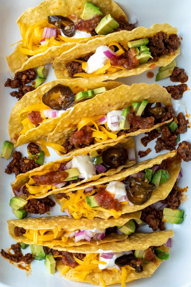 Closeup of beef tacos with toppings.