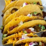 Assembled beef tacos with toppings.