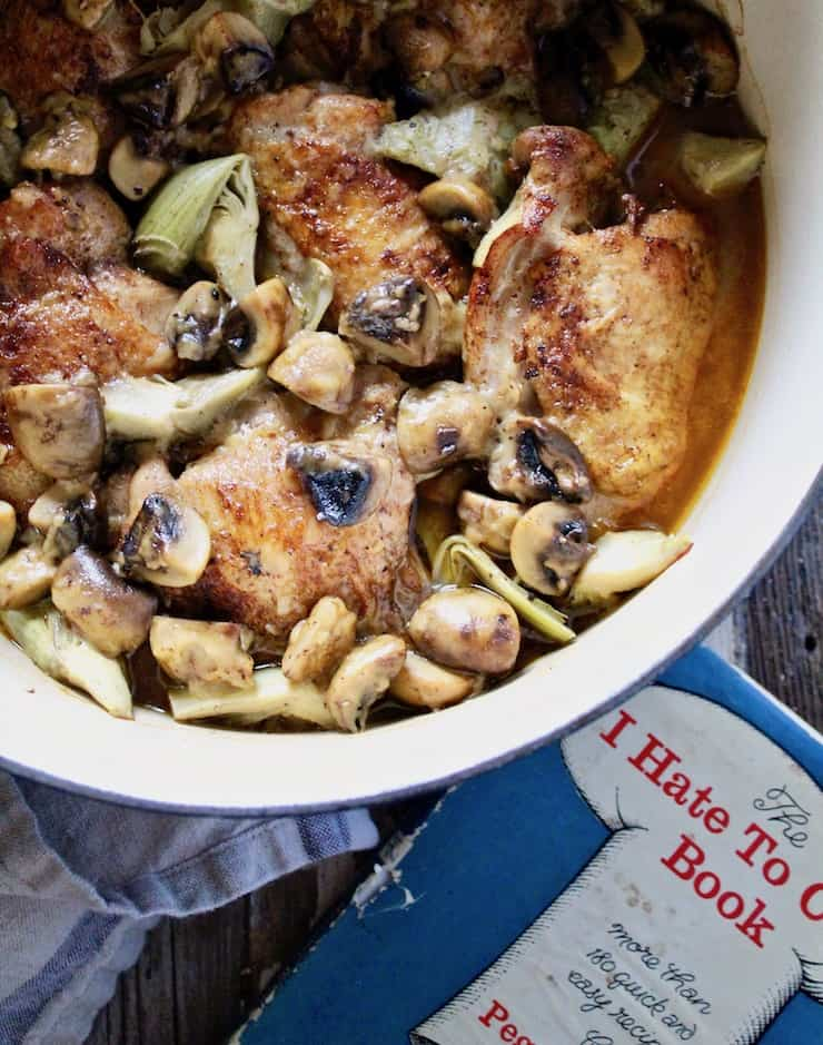 Braised Chicken with Artichokes in Mushroom-Sherry Sauce, with cookbook next to pot of chicken.