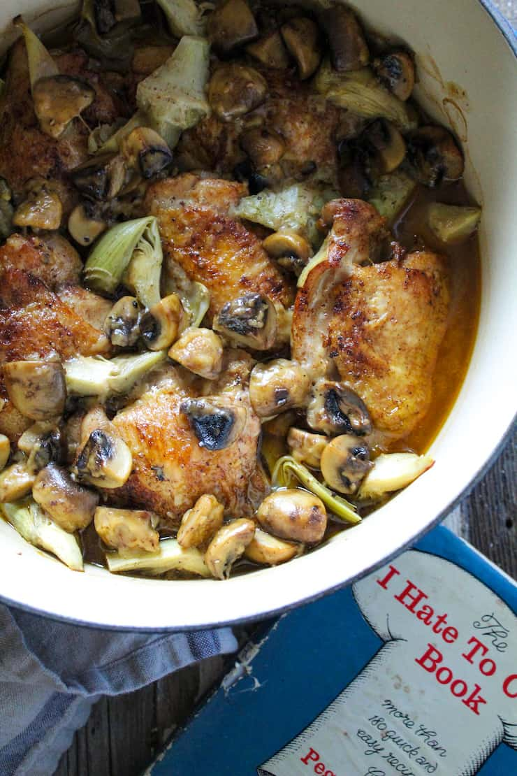 Close up of chicken dish and cookbook.