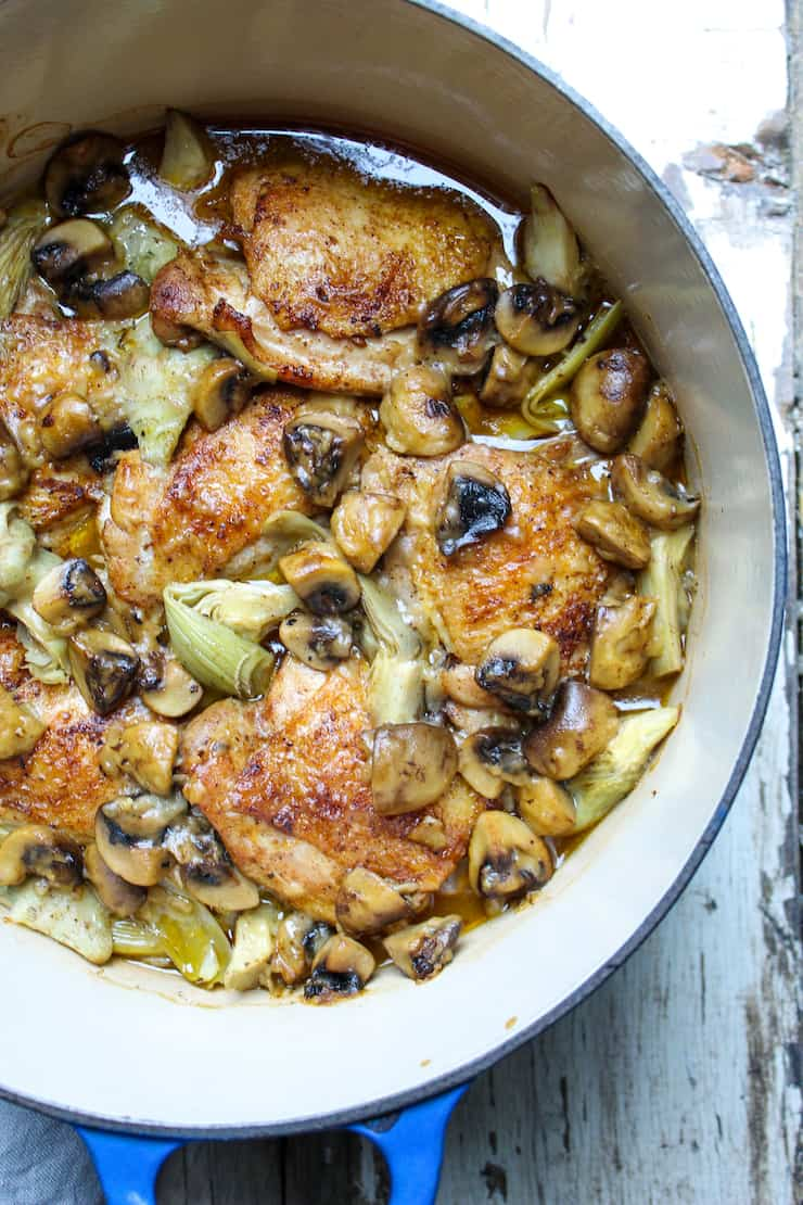 Chicken with artichokes and mushrooms in Dutch oven.