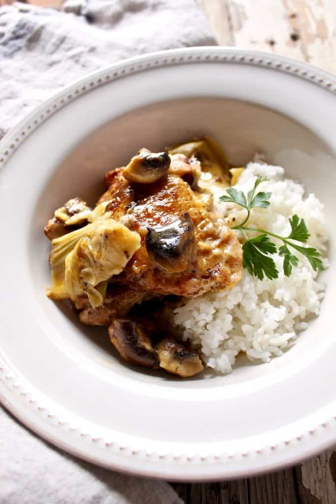 Braised Chicken with Artichokes in Mushroom-Sherry Sauce, plated in dish with rice