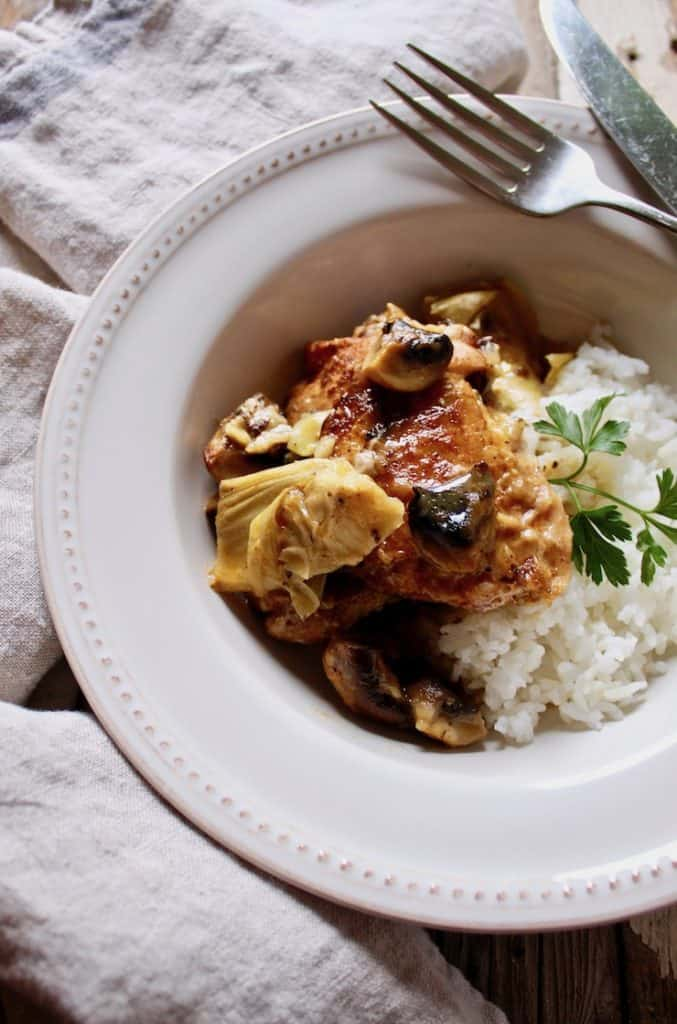 Braised Chicken with Artichokes in Mushroom-Sherry Sauce, plated with rice and knife and fork on side