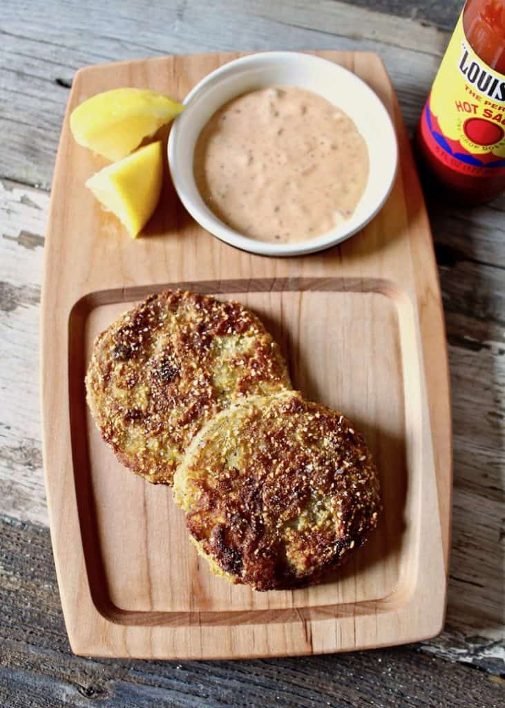 Southern fried green tomatoes on serving board with remoulade sauce, lemons and hot sauce