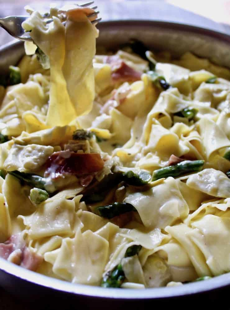Pasta with Asparagus and Prosciutto in skillet with forkful of pasta above pan.