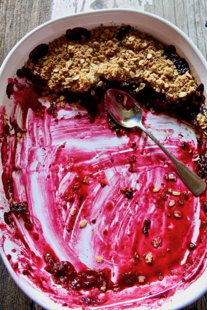 Fresh Blackberry Crisp in baking dish with spoon almost completely eaten.