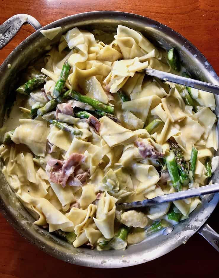 Pasta with Asparagus and Prosciutto overhead photo in skillet with tongs.