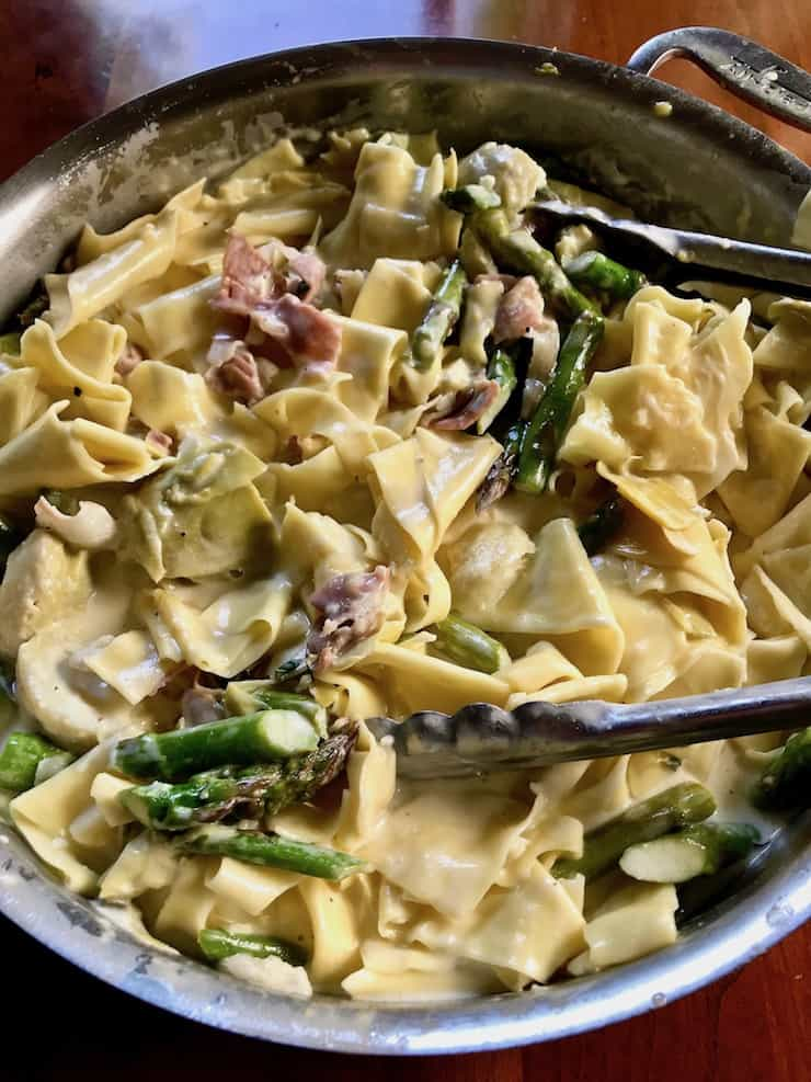 Overhead shot of Pasta with Asparagus and Prosciutto with tongs