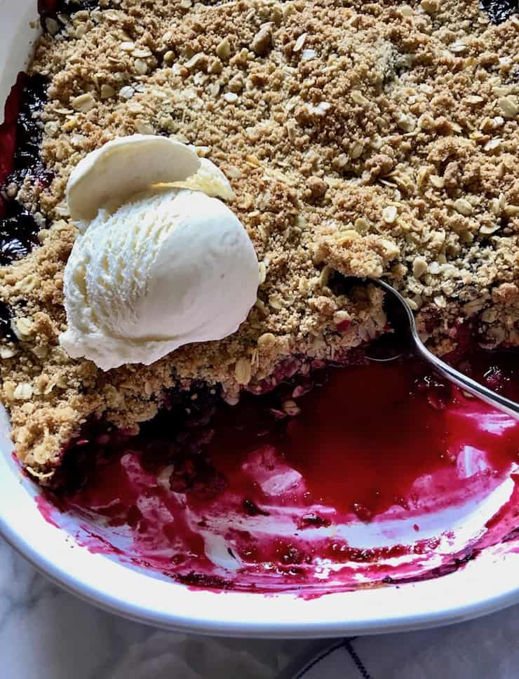 Fresh Blackberry Crisp in baking dish with ice cream and spoon.