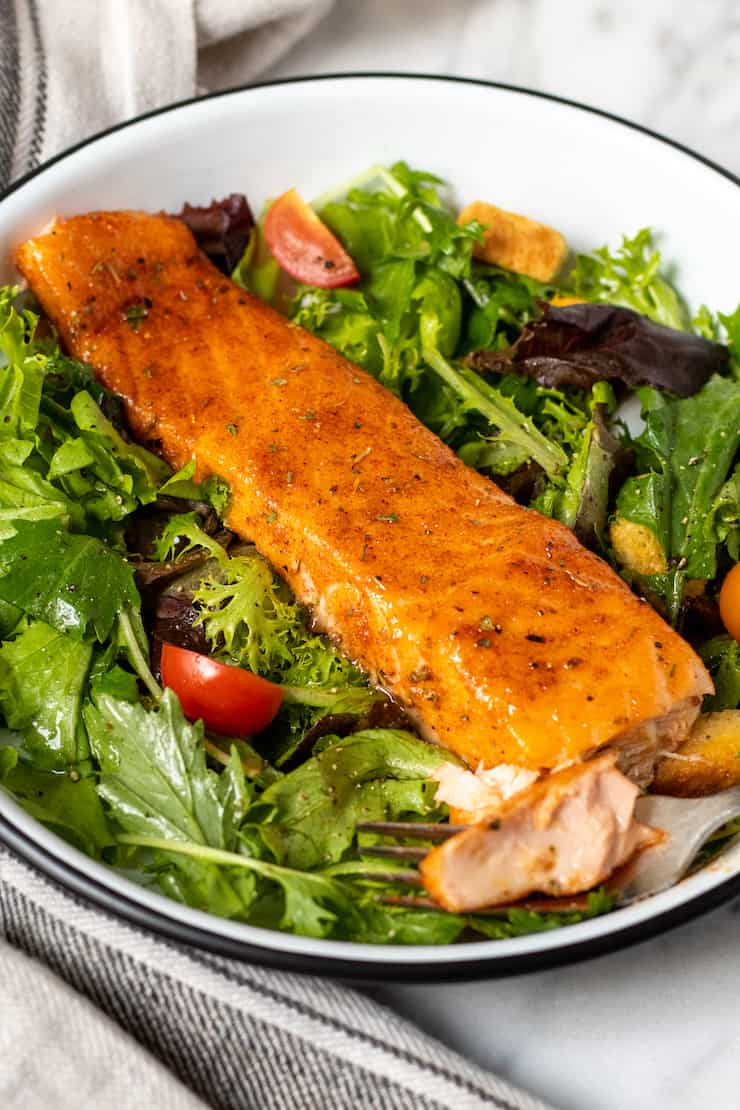 Cajun brown sugar salmon plated with salad greens.