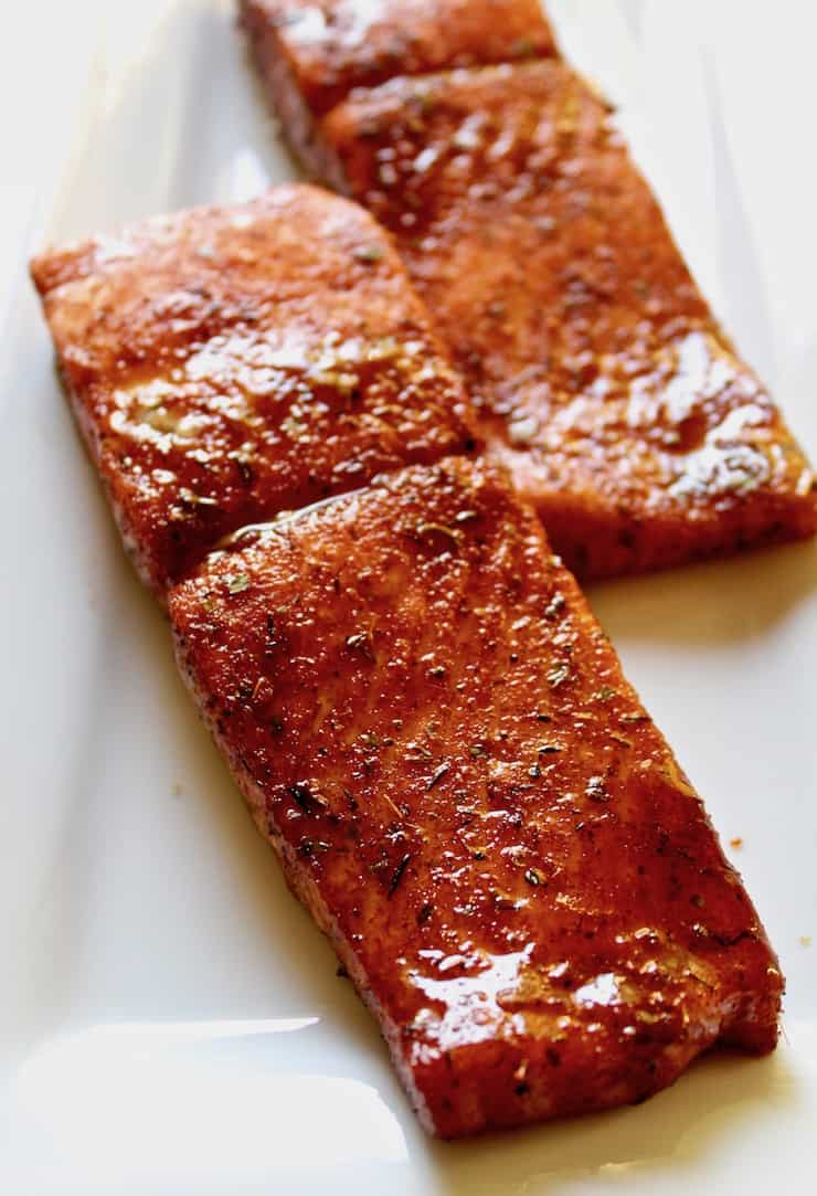 Cajun Brown Sugar Salmon, close up on plate of two baked pieces