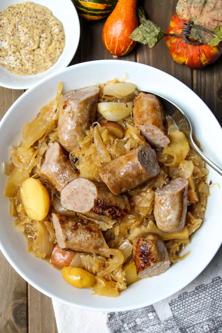 German sausage skillet in white serving bowl with cut up sausage.