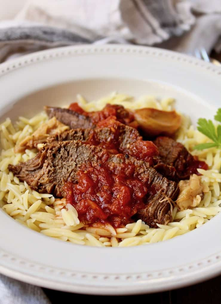Close up sliced beef roast over orzo with sauce and garlic.