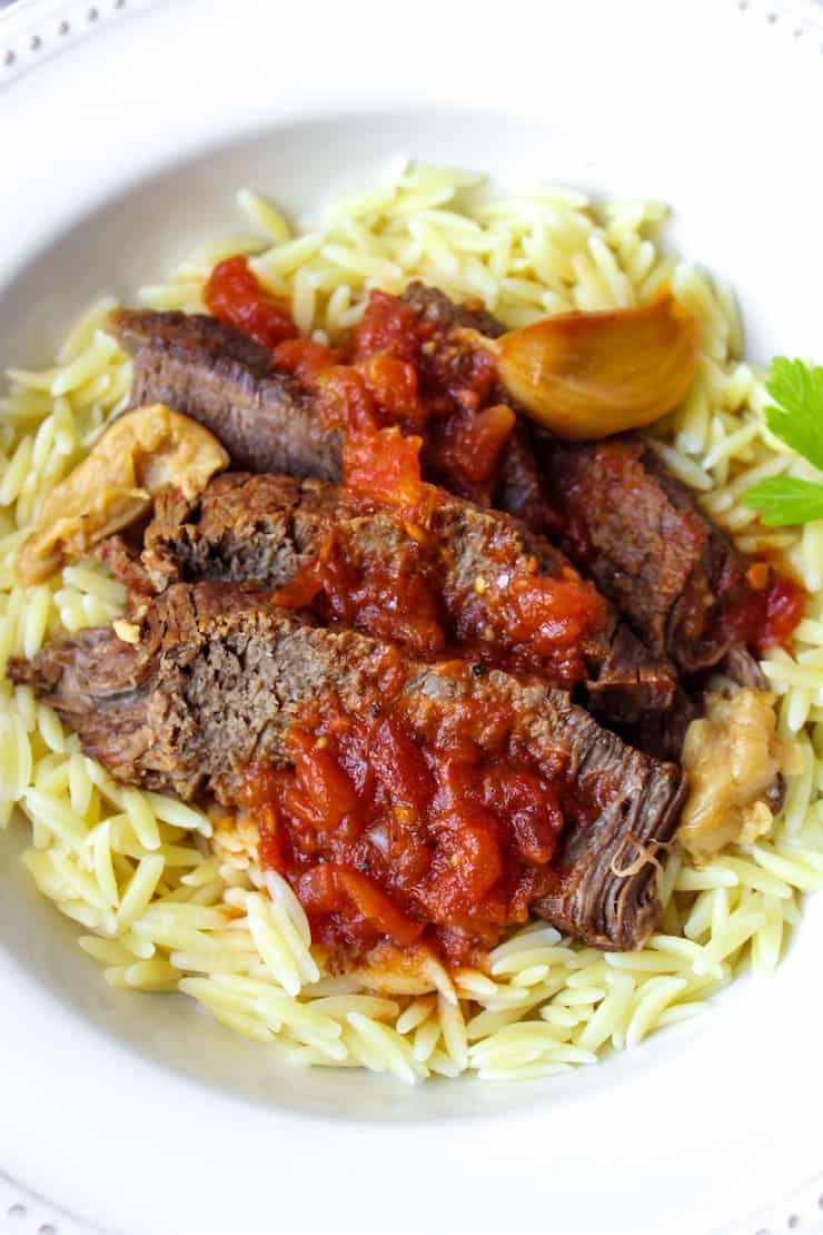 Sliced beef roast served over orzo pasta.