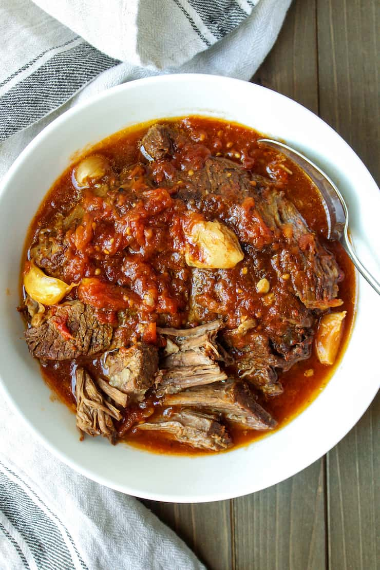 Pot roast and garlic in serving bowl.