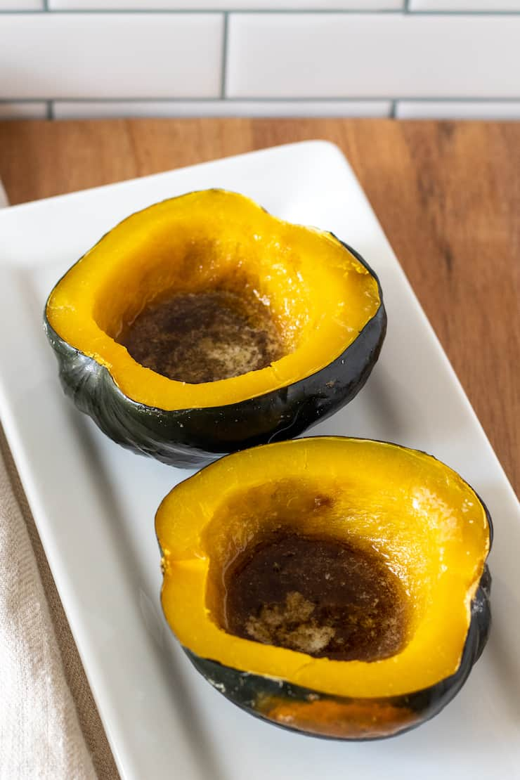 Baked acorn squash with butter and brown sugar on white platter.