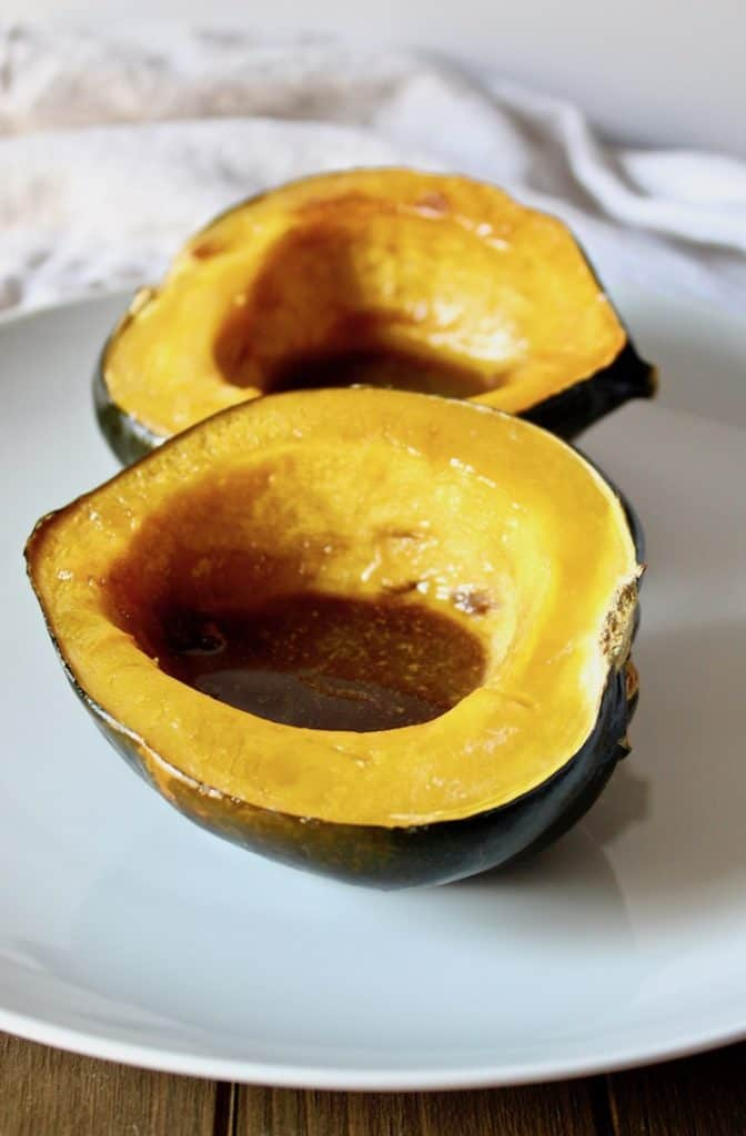 Baked Acorn Squash, on serving plate with melted butter and brown sugar mixture in center cavity.