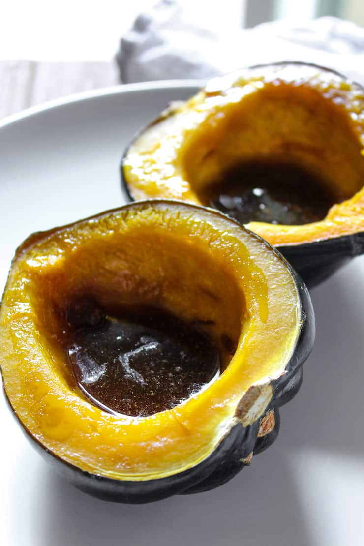 Close up of baked squash with melted butter and brown sugar in cavity.