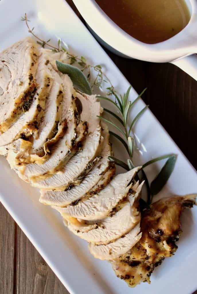 Herb Butter Instant Pot Turkey Breast, sliced on platter with herbs and gravy boat on side