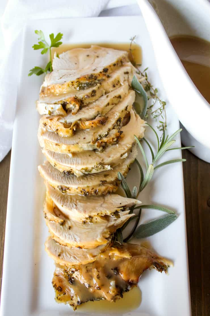 Platter of sliced turkey breast drizzled with gravy.